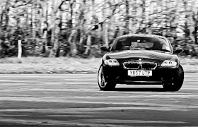 A BMW with wheels at a suspicious angle and the background blurred
